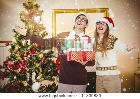 Smiling man and woman wearing Santa hats and holding gifts against christmas tree in living room