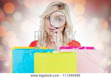 Fair-haired woman looking through a magnifying glass against glowing christmas background