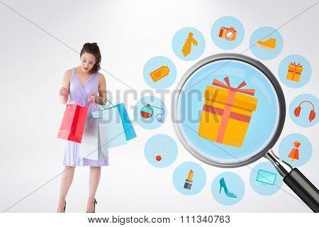 Stylish brunette in purpul dress opening shopping bag against online shopping wheel