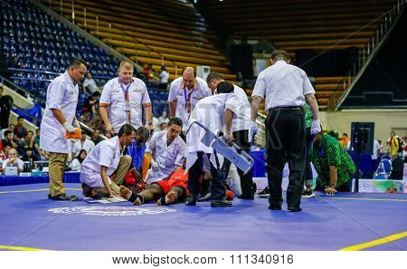 JAKARTA, INDONESIA - NOVEMBER 17, 2015: Fanny Dago of Ivory Coast (red) receives medical attention after a knock-out kick in the men's 90kg Sanda event at the 13th World Wushu Championship 2015.