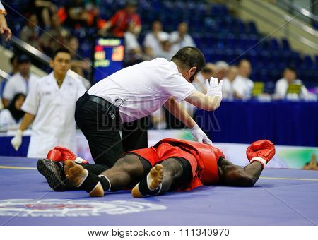 JAKARTA, INDONESIA - NOVEMBER 17, 2015: Fanny Dago of Ivory Coast (red) falls from a back-kick by Abdyraimov Kuan of Krygystan in the men's 90kg Sanda event at the 13th World Wushu Championship 2015.