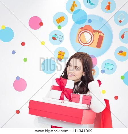 Happy brunette holding christmas gifts and shopping bags against dot pattern