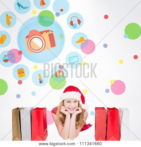 Smiling woman lying between shopping bags against dot pattern