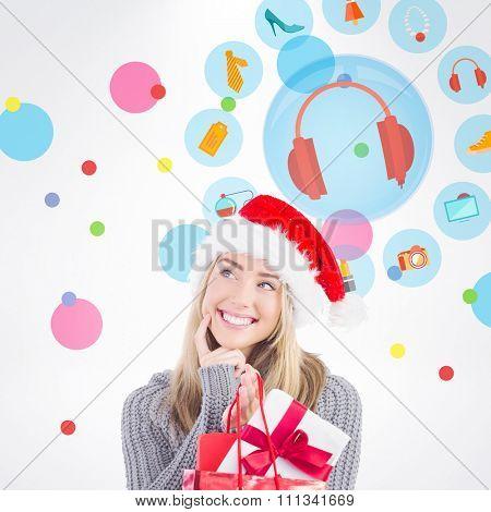 Festive blonde holding christmas gift and bag against dot pattern