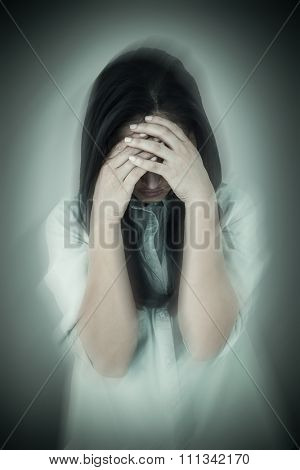 Troubled woman crying against grey vignette