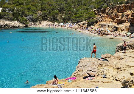 SAN ANTONIO, SPAIN - JUNE 18: Sunbathers at Cala Salada beach on June 18, 2015, in San Antonio, Ibiza Island, Spain. Ibiza is a well-known summer tourist destination in Europe