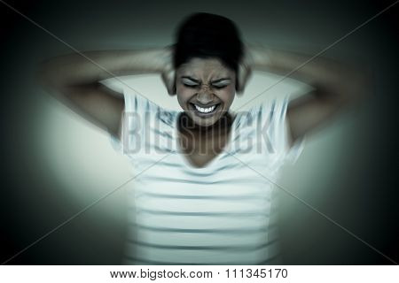 Angry woman covering ears against grey vignette