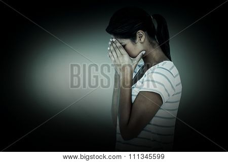 Side view of upset woman covering face against grey vignette