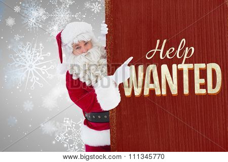 Smiling santa claus pointing poster against vintage help wanted sign