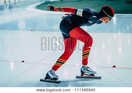 side view young woman athlete speedskater goes around turn sprint distance