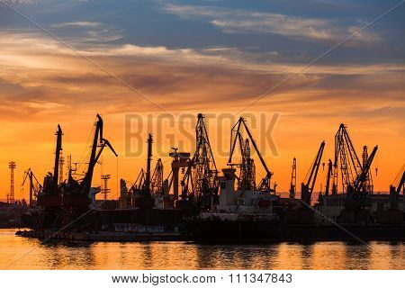Cranes And Cargo Ships In Varna Port At Sunset