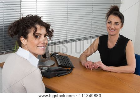 Female Candidate Giving File To Businesswoman At Office Desk