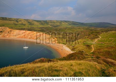 Worbarrow Bay east of Lulworth Cove and near Tyneham on the Dorset coast England uk with a yacht