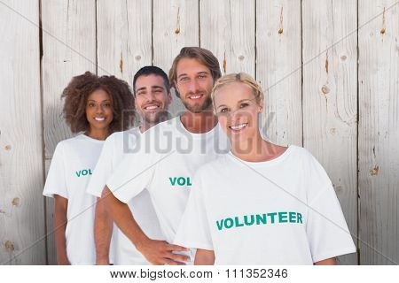 Smiling volunteer group against wooden background