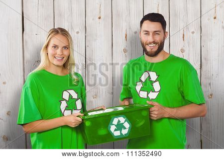 Portrait of smiling volunteers carrying recycling container against wooden background
