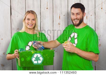 Portrait of happy man holding bottle against wooden background