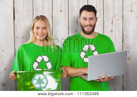 Portrait of smiling volunteers in recycling symbol tshirts against wooden background