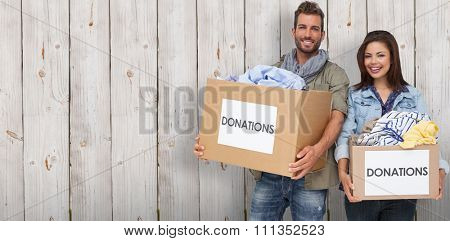 Portrait of a happy young couple with clothes donation against wooden background