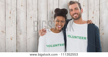 Portrait of two young volunteers with arms around against wooden background