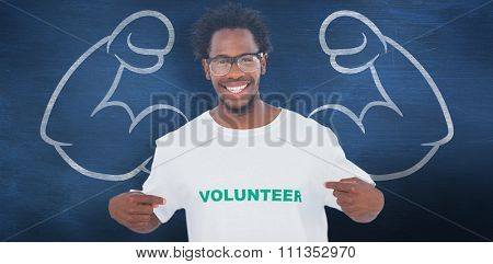 Handsome man pointing to his volunteer tshirt against blue chalkboard