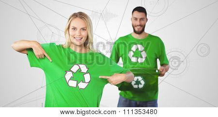 Portrait of woman pointing towards recycling symbol on tshirts against interface with graphs