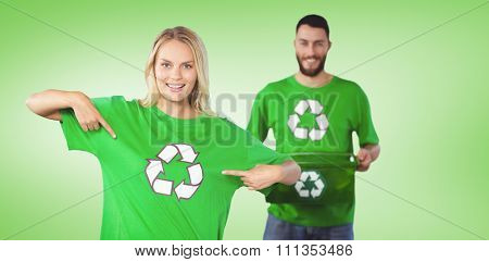 Portrait of woman pointing towards recycling symbol on tshirts against green vignette