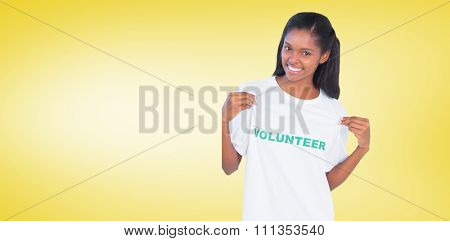 Young woman wearing volunteer tshirt and pointing to it against yellow vignette