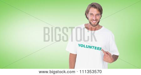 Smiling man pointing to his volunteer tshirt against green vignette