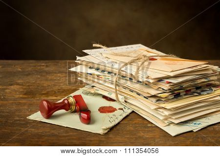 Wax seal next to a bundle of old letters on an antique wooden table