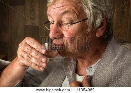 Gray elderly man enjoying a jenever drink in a shot glass