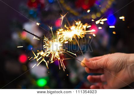 Soft and blur conception.Female hand holding a burning sparklers closeup. New Year's and Christmas