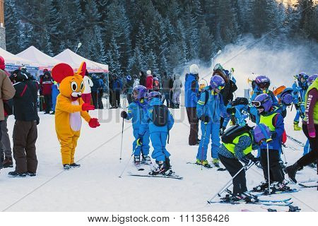 Young skiers preparing to ski and Mouse in Costume, Bansko, Bulgaria