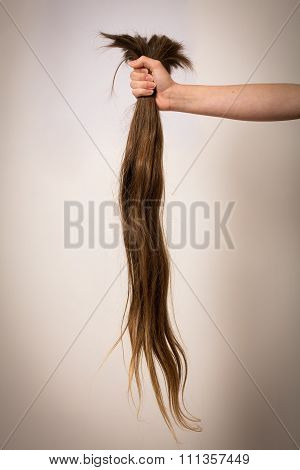 Out Stretched Arm Holding Long Cut Off Hair