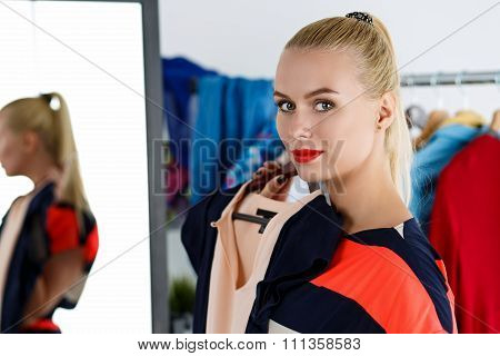 Beautiful Blonde Woman Standing Near Wardrobe Rack Full Of Clothes