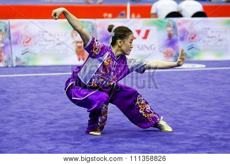 JAKARTA, INDONESIA - NOVEMBER 17, 2015: Gayeong Je of South Korea performs the movements in the women's Compulsory Changquan event at the 13th World Wushu Championship 2015 in Istora Senayan Stadium.