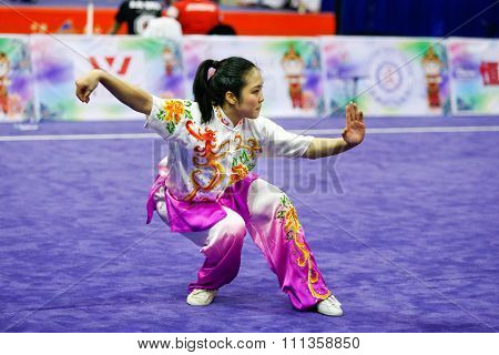 JAKARTA, INDONESIA - NOVEMBER 17, 2015: Ami Li of the USA performs the movements in the women's Compulsory Changquan event at the 13th World Wushu Championship 2015 at the Istora Senayan Stadium.