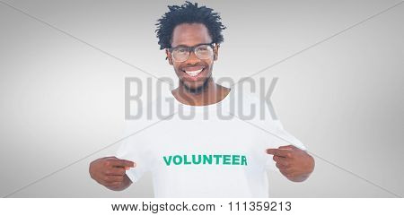 Handsome man pointing to his volunteer tshirt against grey vignette