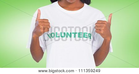 Woman wearing volunteer tshirt and giving thumbs up against green vignette