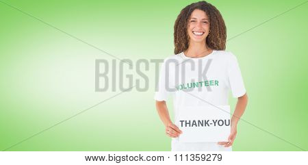 Smiling volunteer showing a thank you poster against green vignette