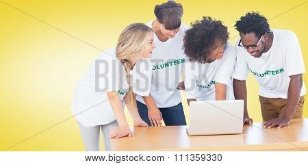 Smiling volunteers working together on a laptop against yellow vignette