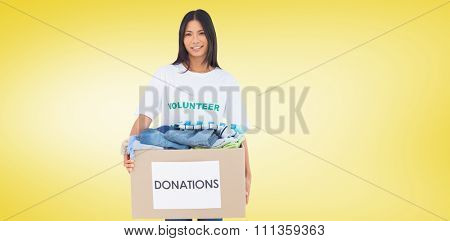 Happy woman carrying donation box against yellow vignette