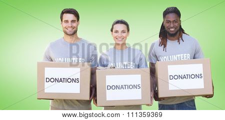 Happy volunteers with donation boxes in park against green vignette