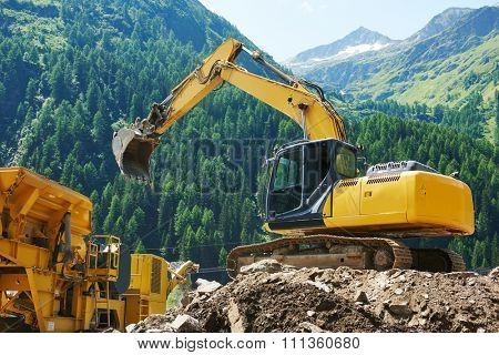 excavator loader machine loading dumper truck at construction site