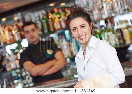 waitress restaurant catering service. Female cheerful restaurant worker with barman at background