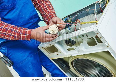 Washing machine repair. Repairer hands replasing with water level sensor pressure switch in front of damaged unit