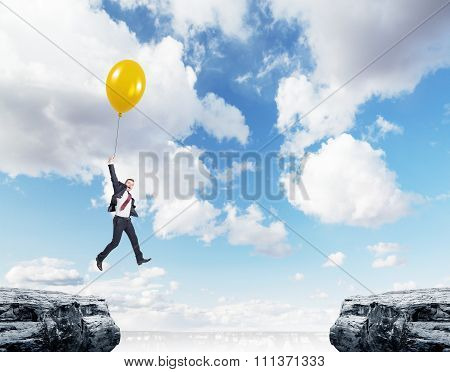 Man Flying Between Two Cliffs