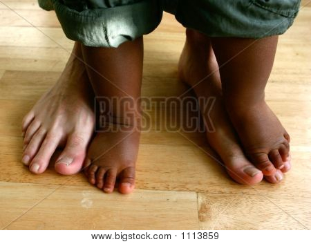 Two Pairs Of Feet Belonging To A Father And His Little Toddler Son.