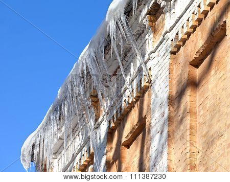 Snow-covered Roof Of Old House With Icicles