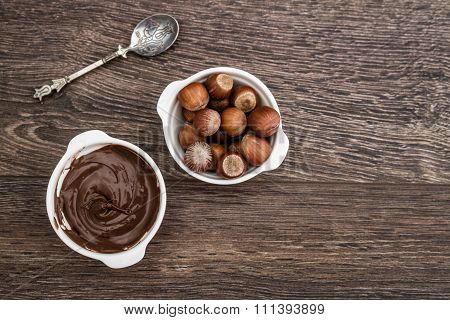 Chocolate Cream And Hazelnuts In White Bowls On Brown Wooden Table