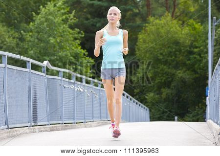 Young running woman trains her stamina outdoor